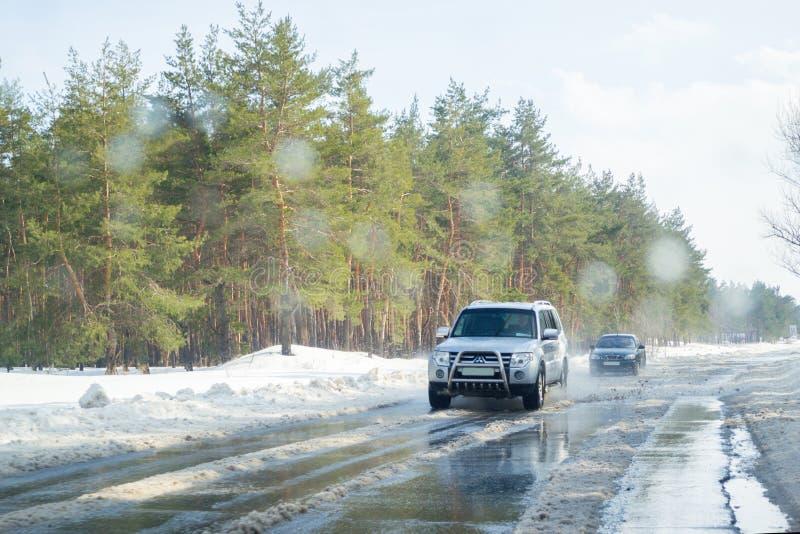 Het drijven op een sneeuwweg in de winter of de vroege lente Weergeven van het autoraam op de weg met smeltende sneeuw op het stock fotografie
