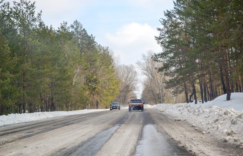 Het drijven op een sneeuwweg in de winter of de vroege lente Weergeven van het autoraam op de weg met smeltende sneeuw op het royalty-vrije stock fotografie