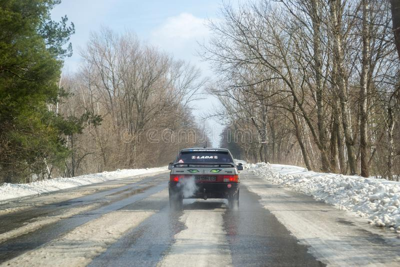 Het drijven op een sneeuwweg in de winter of de vroege lente Weergeven van het autoraam op de weg met smeltende sneeuw op het stock afbeelding