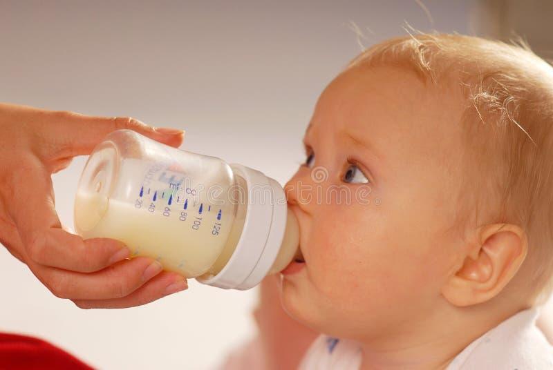 Het drinken van de baby melk stock fotografie