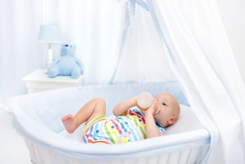 Het drinken van de baby melk Jongen met formulefles in bed stock afbeeldingen