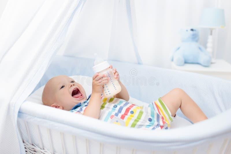Het drinken van de baby melk Jongen met formulefles in bed stock foto