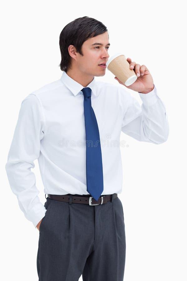 Het drinken van de kleinhandelaar koffie uit een document kop stock afbeeldingen