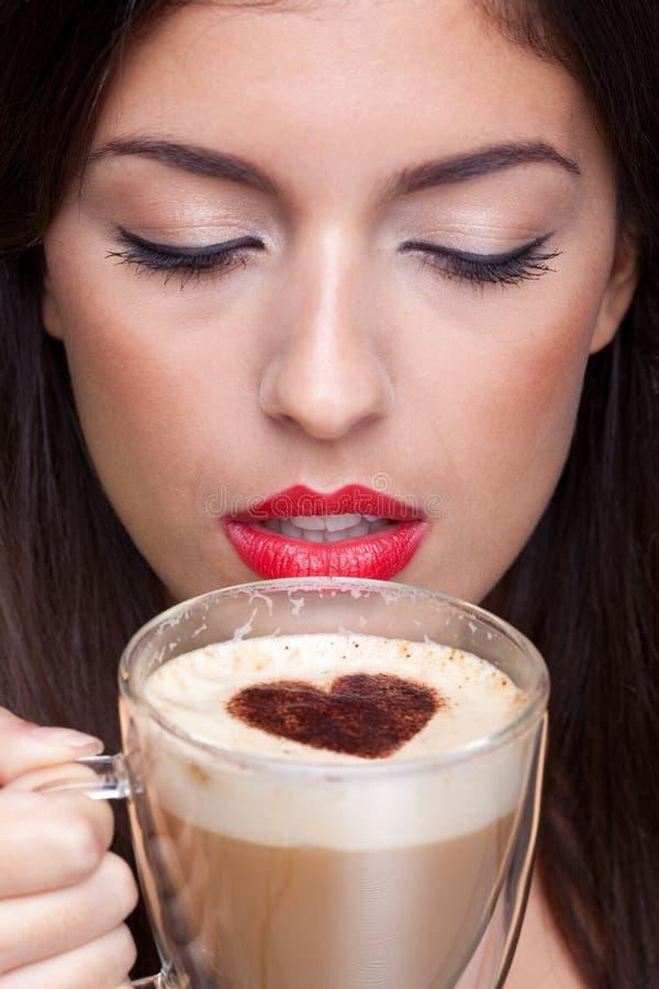 Het drinken van de vrouw cappuccino'skoffie met liefdehart s stock afbeelding