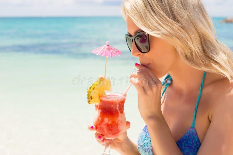 Het drinken van de vrouw cocktail op het strand stock afbeeldingen