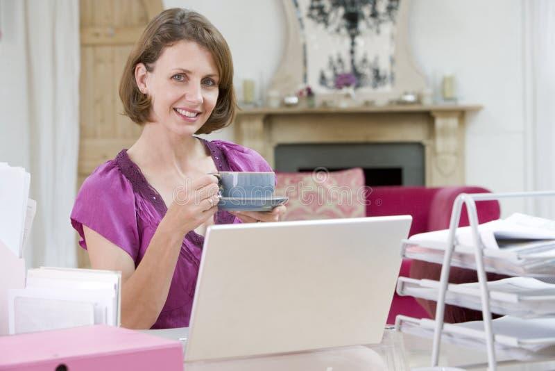 Het drinken van de vrouw koffie bij haar bureau stock afbeelding