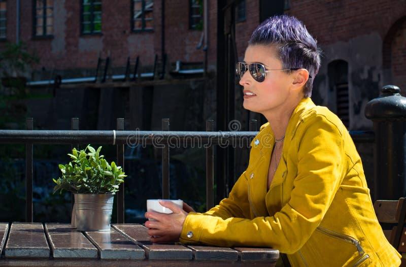 Het drinken van de vrouw koffie buiten stock foto