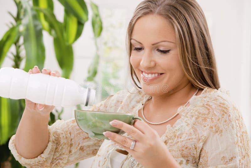 Het drinken van de vrouw yoghurt stock foto's