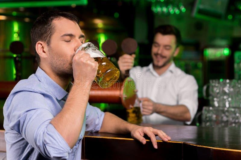 Het drinken van een vers onttrokken bier. stock fotografie