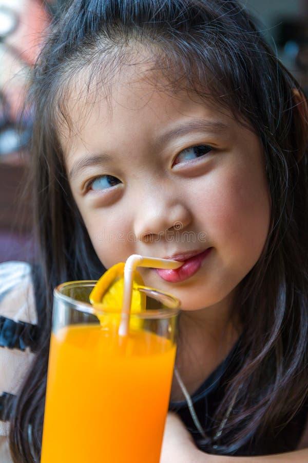 Het drinken van het kind jus d'orange stock afbeelding