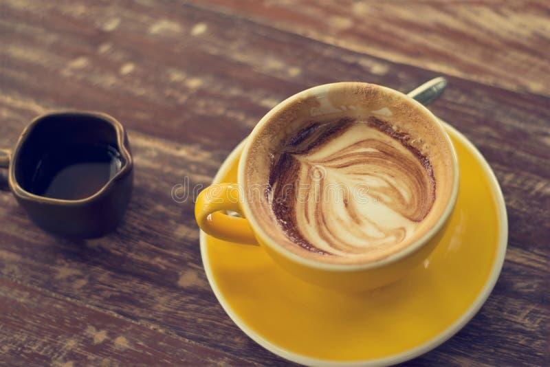 Het drinken van koffie was verminderd aan de helft van een kop op houten lijst royalty-vrije stock foto's