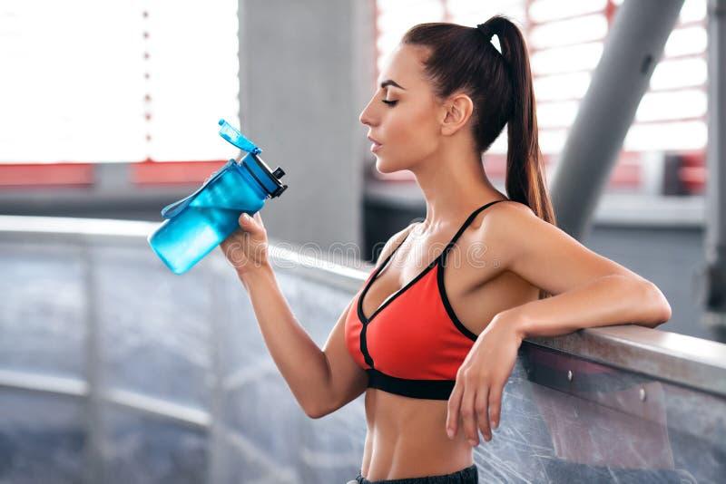 Het drinkwater van de geschiktheidsvrouw van een fles Het jonge actieve meisje dooft dorst royalty-vrije stock foto