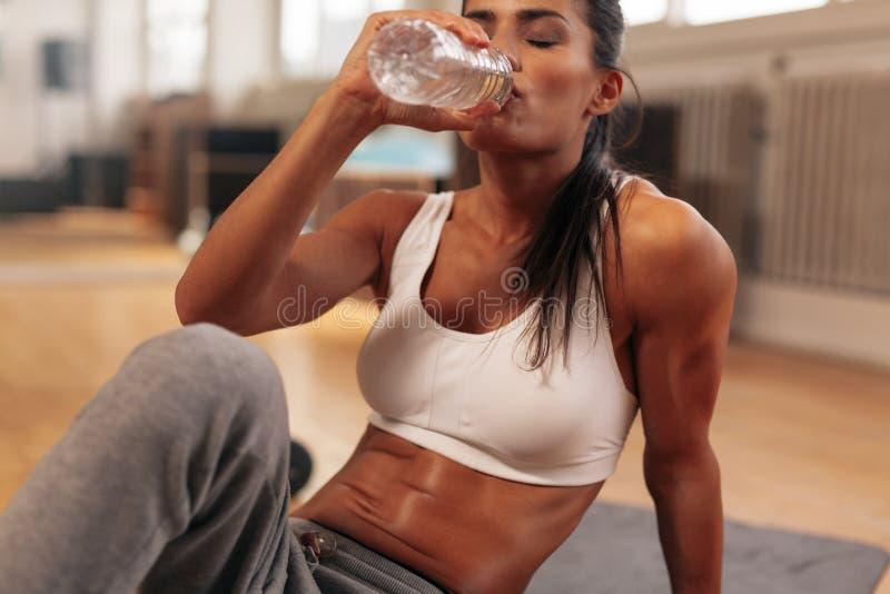 Het drinkwater van de geschiktheidsvrouw van fles bij gymnastiek stock afbeeldingen