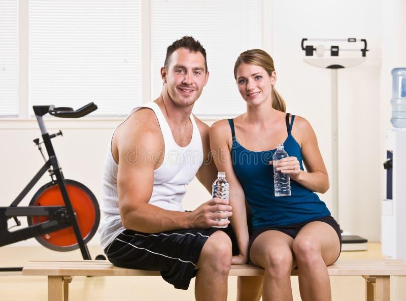 Het drinkwater van de man en van de vrouw in gezondheidsclub stock afbeeldingen
