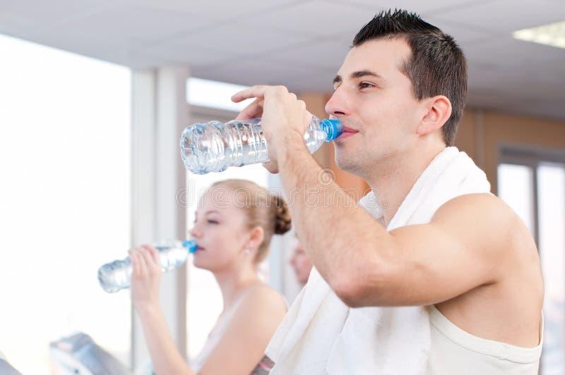 Het drinkwater van de man en van de vrouw na sporten in gymnastiek stock fotografie