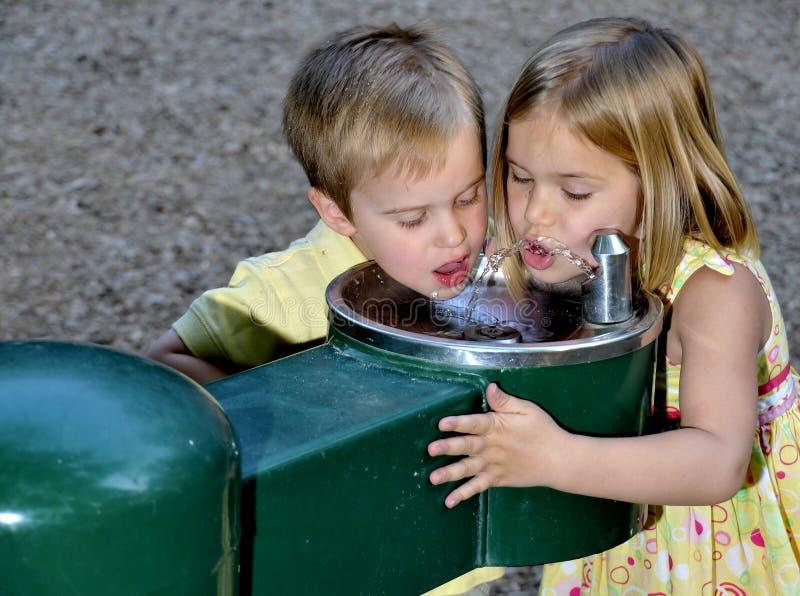 Het Drinkwater van jonge geitjes royalty-vrije stock foto