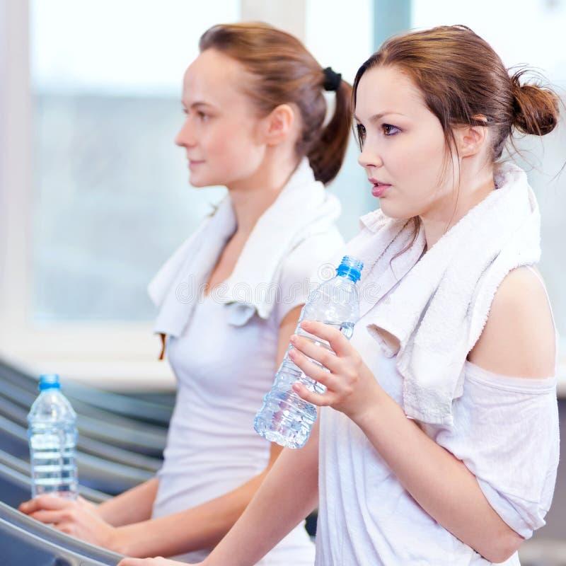 Het drinkwater van vrouwen na sporten stock foto