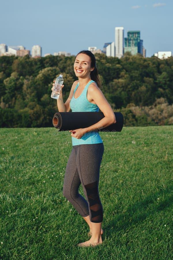 Het drinkwater van het yogimeisje na training royalty-vrije stock afbeelding