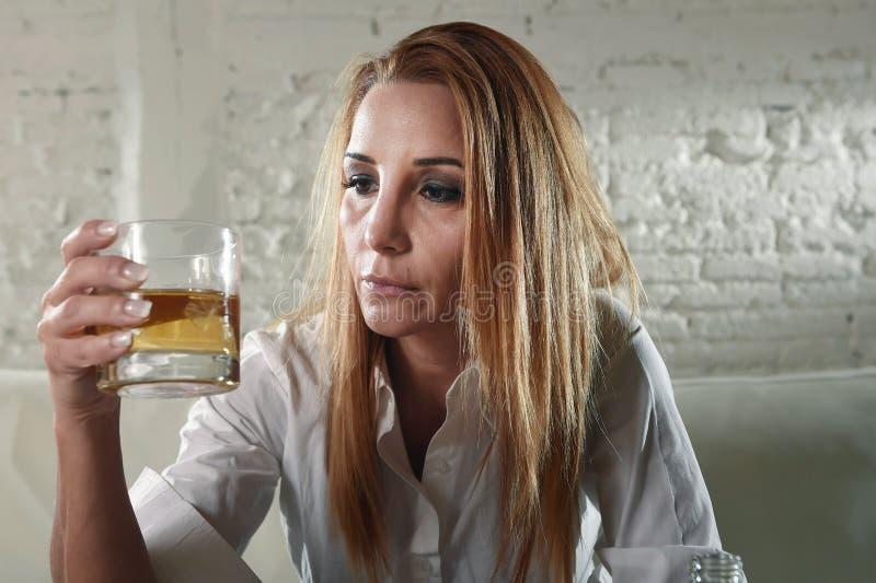 Het droevige gedeprimeerde alcoholische gedronken vrouw drinken thuis in het misbruik en het alcoholisme van de huisvrouwenalcoho stock afbeelding