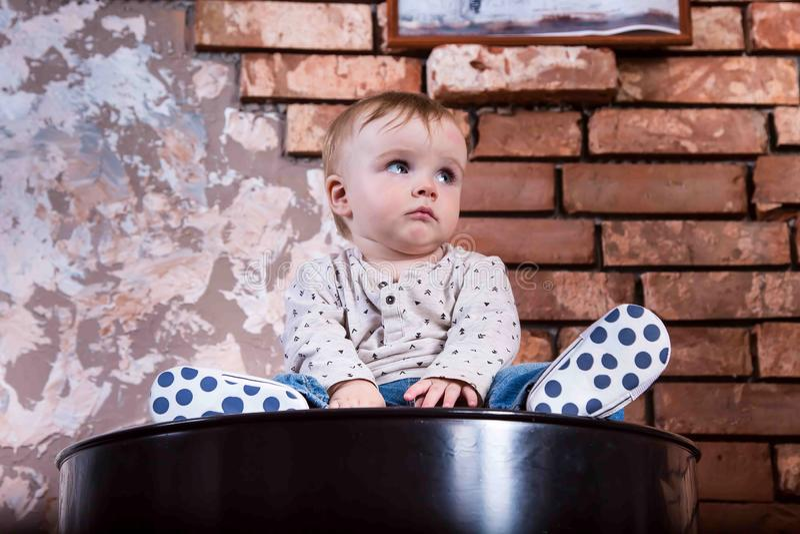 Het droevige kleine kind zit op een de Babyjongen van het ijzervat op de achtergrond van een bakstenen muur royalty-vrije stock foto