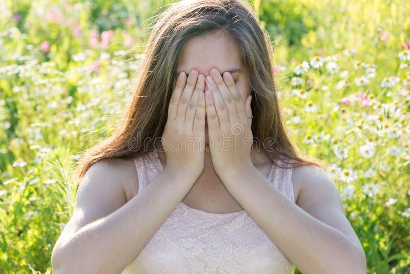 Het droevige meisje behandelt gezicht met haar handen en huilt stock afbeelding