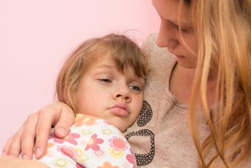Het droevige meisje van vijf jaar klampte zich aan haar moeder vast stock fotografie
