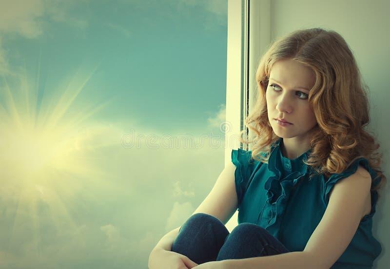 Het droevige, mooie meisje pining bij venster royalty-vrije stock afbeelding