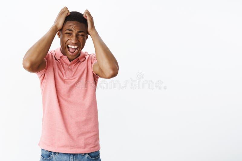 Het droevige ontstemde en geërgerde Afrikaanse Amerikaanse jonge gevoel van de kerel verliezende die bui van leugens omhoog wordt stock fotografie