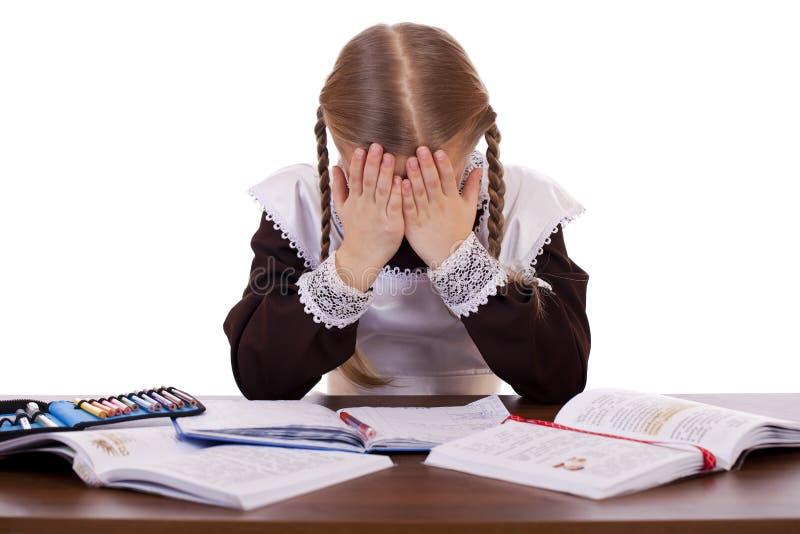 Het droevige schoolmeisje zit bij een schoolbank royalty-vrije stock afbeelding