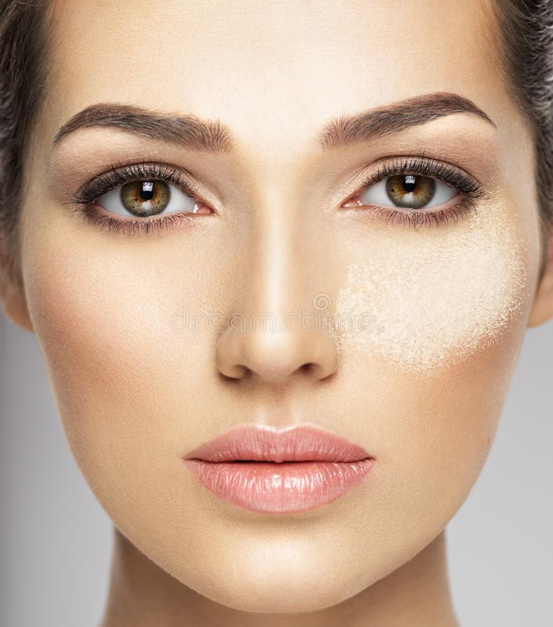Het droge kosmetische make-uppoeder is op het vrouwelijke gezicht royalty-vrije stock afbeelding