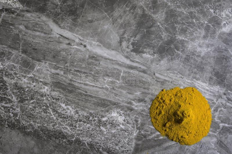 Het droge organische poeder van de kurkumawortel op een marmeren keuken worktop achtergrond stock afbeeldingen