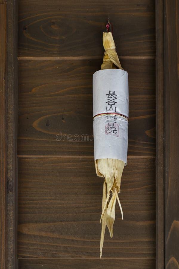 Het droge suikermaïs hangen in deuropening bij handelaarshuis stock afbeelding