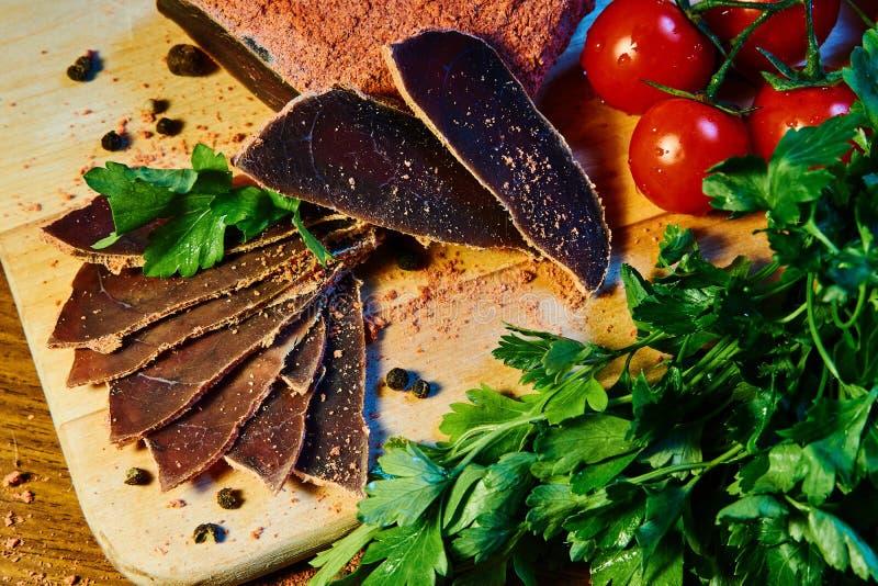 Het droge vlees, basturma ligt op een houten Raad met kappertjes en kruiden verse peterselie en rode kersentomaten stock foto