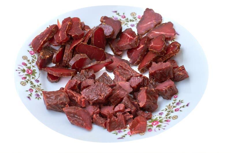 Het droge vlees, basturma, schokkerig rundvlees, rookte vlees schokkerig met kruiden op een plaat, isoleert close-up stock afbeeldingen