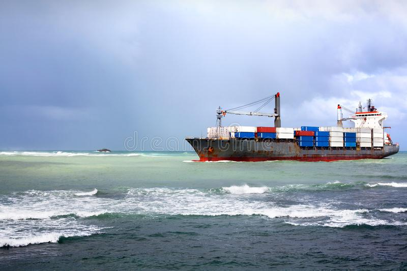 Het droge vrachtschip, bulk-carrierschip met containers gaat aan boord de overzeese haven in een zeehaven in stock afbeelding