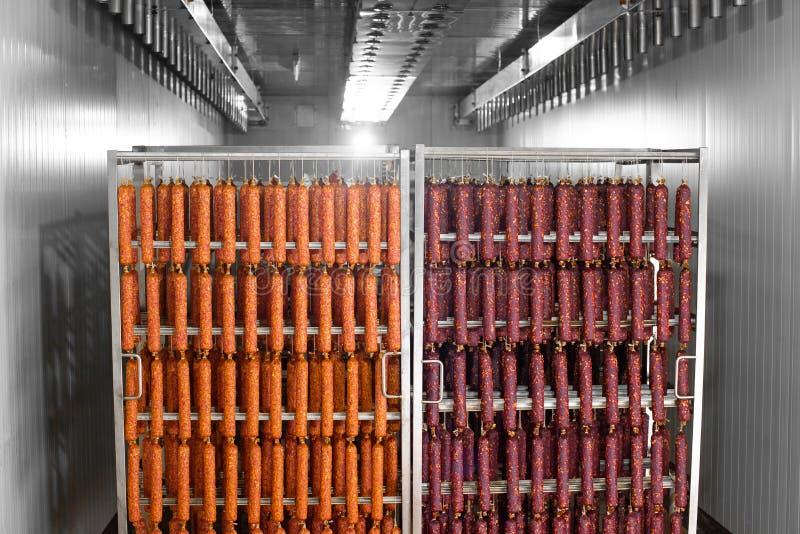 Het droge worst hangen op een kabel op een metaalkader in het rookhuis stock afbeelding