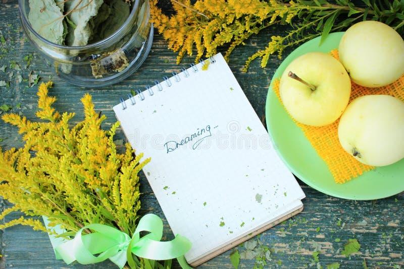 Het dromen thema, contrast van groene en gele kleur: appelen, bos van wilde bloemen, notitieboekje op ruwe houten lijst stock foto's