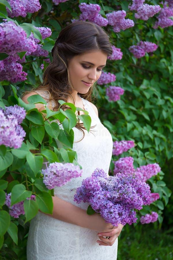 Het dromen van het mooie bruid stellen dichtbij bloeiende lilac boom stock afbeelding