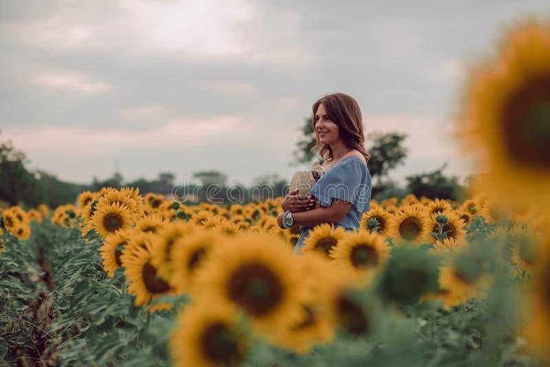 Het dromen van jonge vrouw die in blauwe kleding een hoed op een gebied van zonnebloemen houden bij de zomer, mening van haar kan stock foto's