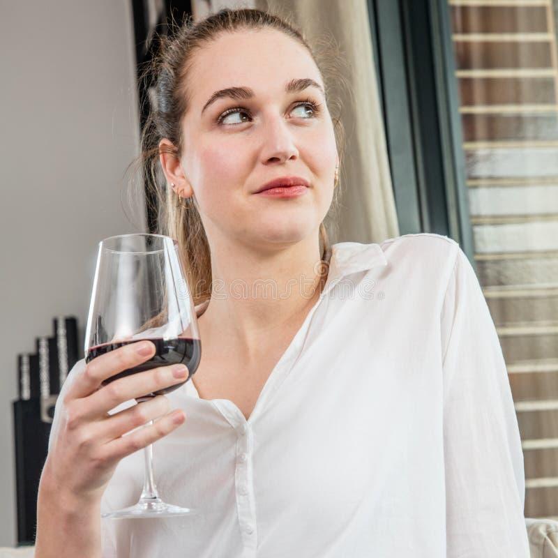 Het dromen van mooie jonge vrouw die van het glas van de holdingswijn voor degustation genieten royalty-vrije stock fotografie
