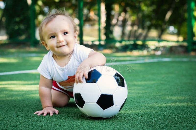 Het dromen van weinig jongen bij het stadion met een voetbalbal Toekomstige voetbalster stock foto's