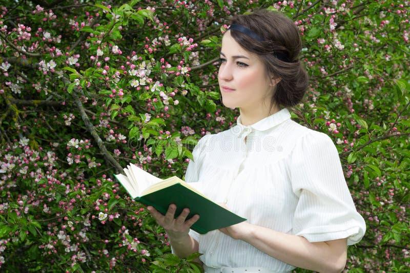 Het dromerige mooie boek van de vrouwenlezing in bloeiende de lentetuin stock afbeelding