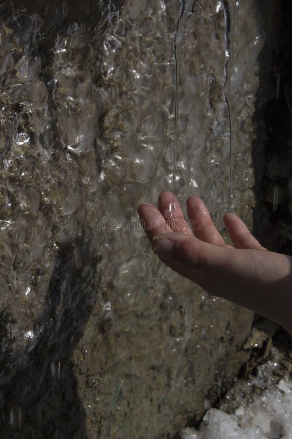 Het druipen dalingen van smeltende ijskegels onder de invloed van zonlicht en hand die deze dalingen op de achtergrond van ijzige royalty-vrije stock afbeelding