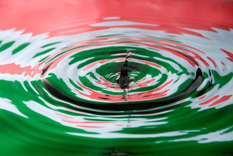 Het druppeltje van het water tegen een vlag van Hongarije stock foto