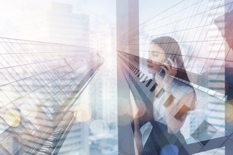 Het dubbele Blootstelling en Technologie Communicatie Concept, Portret van Bedrijfsvrouw spreekt op Mobiele Telefoon in Haar Bure royalty-vrije stock afbeeldingen