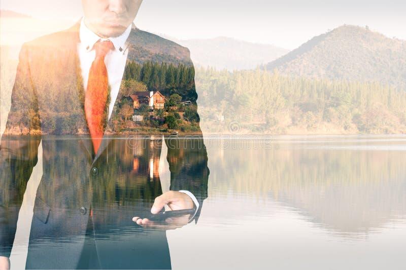 Het dubbele blootstellingsbeeld van de zakenman die een smartphone gebruiken tijdens zonsopgangbekleding met aardbeeld Het concep royalty-vrije stock afbeeldingen