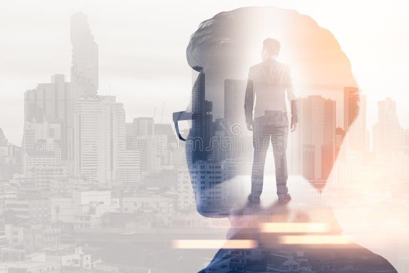Het dubbele blootstellingsbeeld van de zakenman die tijdens zonsopgangbekleding denken met cityscape beeld r stock afbeeldingen