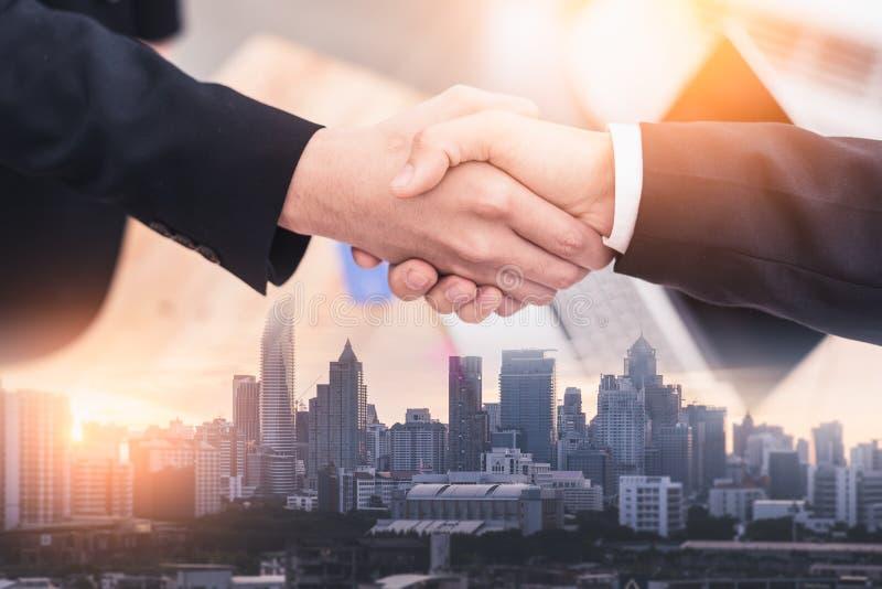 Het dubbele blootstellingsbeeld van het zakenmanhandenschudden met een andere tijdens zonsopgangbekleding met cityscape beeld Het stock foto's