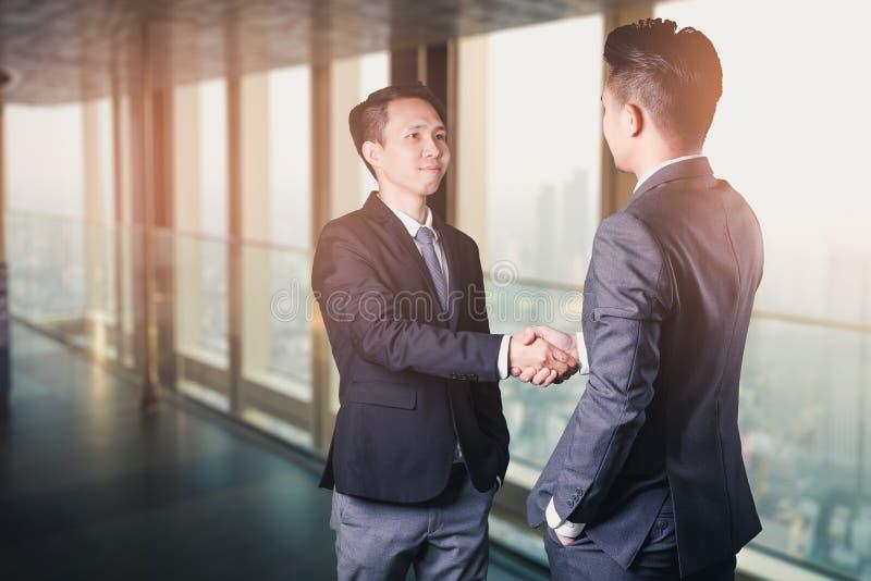 Het dubbele blootstellingsbeeld van het zakenmanhandenschudden met een andere tijdens zonsopgangbekleding met cityscape beeld Het royalty-vrije stock fotografie