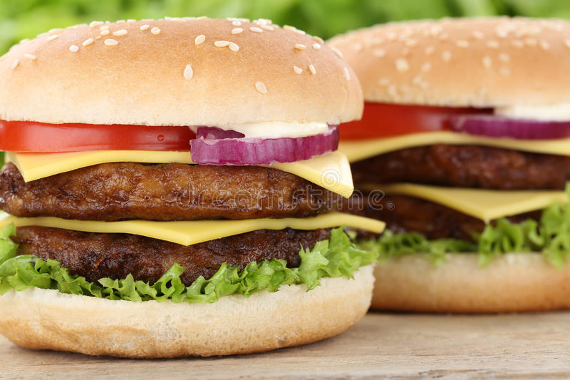 Het dubbele van de de hamburgerclose-up van de cheeseburgerhamburger dichte omhooggaande rundvlees tomat stock fotografie